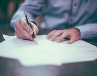 man writes on paper